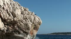 A man jumping into the sea from a rock 2 Stock Footage