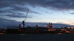 Cargo ship loading under crescent moon  Stock Footage
