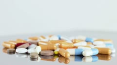 Many colorful pills turning on a plate - stock footage