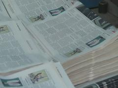 Printing house worker is working on bunch of newspapers. Stock Footage