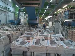 Pile of printed newspapers and workers in printing house. Stock Footage
