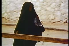 Egyptian woman in full burqa walks carrying shoes 108065 Stock Footage