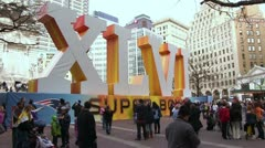 People in front of Super Bowl sign downtown Stock Footage