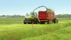 A tractor is harvesting freshly mowed grass - stock footage