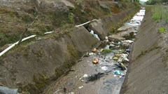 Garbage strewn ditch in small town Stock Footage
