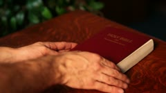 Hands opening a bible on a pulpit - stock footage
