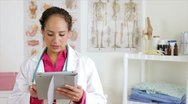 Hispanic doctor with tablet smiles at camera Stock Footage