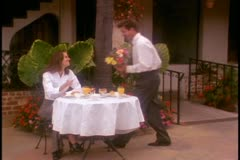 A man brings flowers to his girlfriend at an outdoor cafe Stock Footage