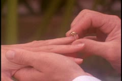 A young man places an engagement ring on the hand of his fiancee Stock Footage