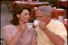 A mature couple have coffee at an outdoor cafe Stock Footage