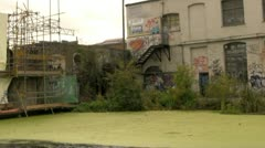 Derelict buildings and graffiti on an urban waterway Stock Footage