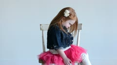 Young girl pouting on chair - stock footage
