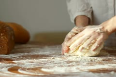 Female hands kneading dough in flour on table - stock footage