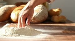 Baker mixing flour on table, dolly shot - stock footage
