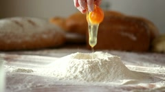 Baker adding egg to flour on table, slow motion Stock Footage