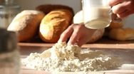 Stock Video Footage of Baker adding milk to flour on table