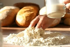 Baker adding milk to flour on table Stock Footage