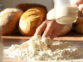 Baker adding milk to flour on table Stock Footage
