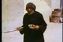 Wadi Naturim monastery and a coptic monk carries two bowls  108166 Stock Footage