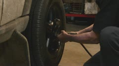 Mechanic taking lugnuts off tire 8017 Stock Footage