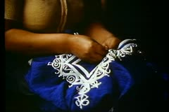 Cairo Bazaar, girl sews embroidery on blue fabric, 2 shots ,medium and close-up Stock Footage