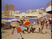 Stock Video Footage of Alexandria, beach, modern skyline, medium shot, umbrellas foreground