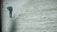 Man with umbrella walking on the snowy sidewalk Stock Footage