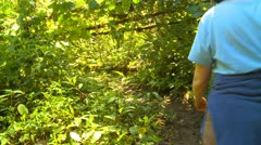 Jungle woman walks through frame Stock Footage