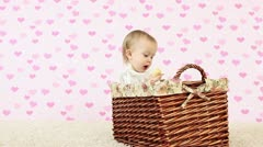 Baby girl eating a banana and sits in a wicker basket Stock Footage