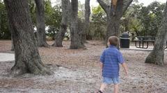 Boy walking around park Stock Footage