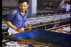 Cotton factory, silk screening, one man, close up, passing brush across Stock Footage