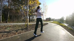 Girl runs through the park in the morning - stock footage