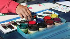 Artist painting watercolor picture paints using dye paint trays in Santa Monica Stock Footage