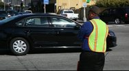 Stock Video Footage of Traffic control person in yellow vest  directing traffic - Santa Monica
