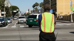 Traffic control officer in yellow vest directing traffic in Los Angeles Stock Footage