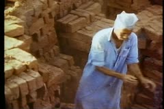Fayoum Oasis, brigade of men tossing bricks to each other, zoom out wide Stock Footage