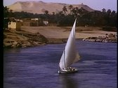 Stock Video Footage of Aswan, Nile River, felucca's (sailboats), medium close up, one boat
