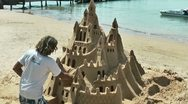 Stock Video Footage of Artist making a sand castle on the beach