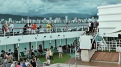 Passengers on cruise ship with panoramic city of Santos behind Stock Footage