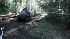 ATV driving over logs in the forest - stock footage