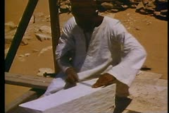 Temples under restoration near Sakkara, close up man filing top of stone Stock Footage