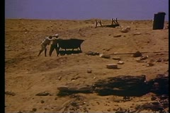 Archeological site near pyramids, group working, hand trucks, medium shot Stock Footage