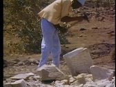 Stock Video Footage of Temples of Philae being rebuilt, one man pounds block with sledgehammer