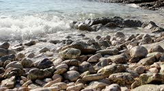 Waves splashing pebble beach Stock Footage