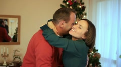 Couple talking and hugging in front of christmas tree Stock Footage