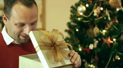 Happy man looking at great gift in the box, christmas tree in background Stock Footage