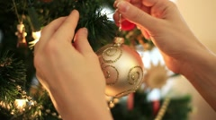 Female hand hangs golden christmas ball on tree, close up Stock Footage