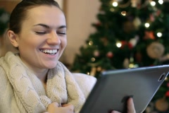 Young happy woman with tablet computer, christmas tree in background Stock Footage