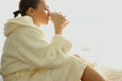 Young attractive woman in bathrobe drinking tea by the window Stock Footage