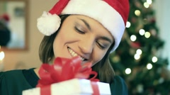 Happy excited woman gets present, christmas tree in background Stock Footage